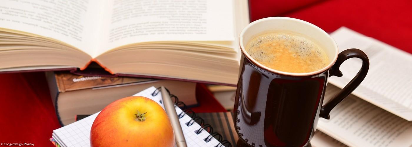 Bücher, Kaffeetasse und Apfel